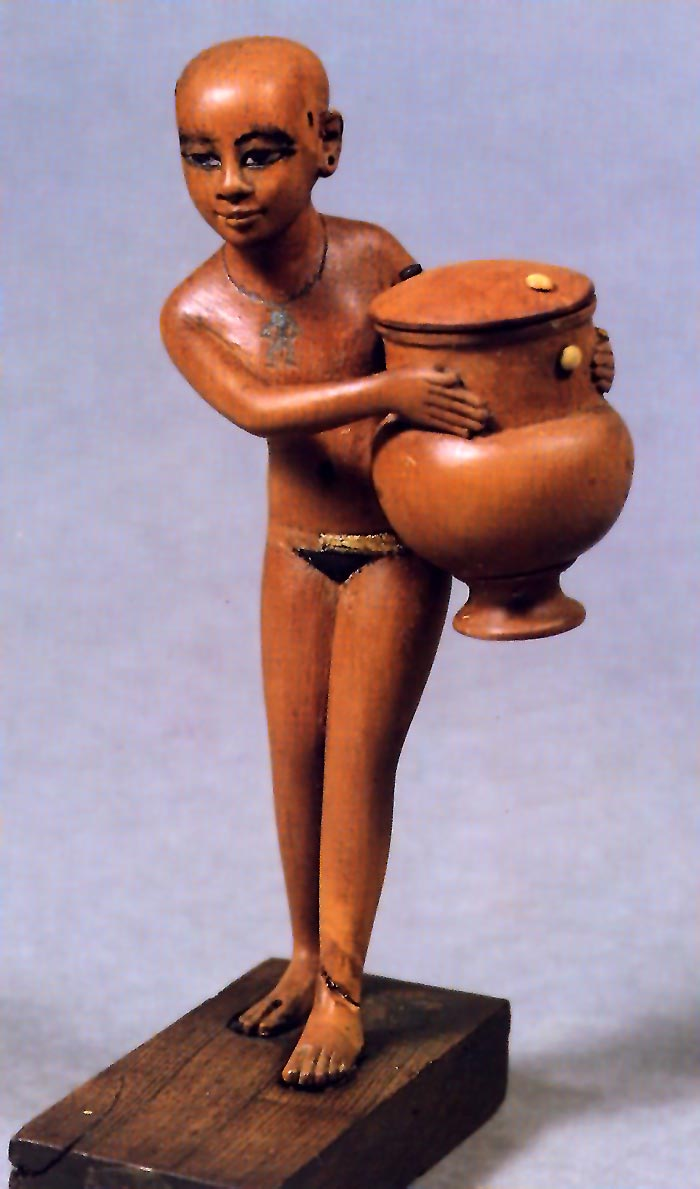 Fig. 8. Ungüentario que muestra a una niña cargada con una gran tinaja. La obra de unos 13 centímetros de alto y conservada en el museo de la Universidad de Durham, es una talla realmente magistral. Muestra como la joven curva la espalda y ladea el cuerpo debido al peso del objeto que sostiene levemente apoyado en su cadera. Foto tomada del Catálogo de la exposición Aménophis III, Le pharaon-soleil, París, 1992, p. 319.