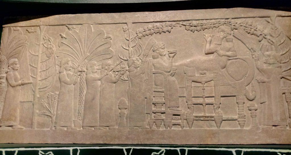 Asurbanipal en palacio con su reina. A destacar la cabeza del rey de Elam en el árbol