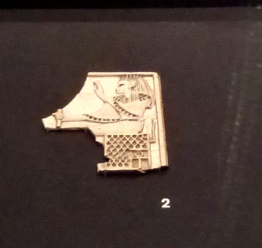 Mujer sentada con vestido y peluca egipcios, y un Ankh